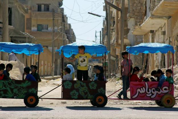 Children ride in carts on the third day of Eid al-Adha in the rebel controlled city of Idlib